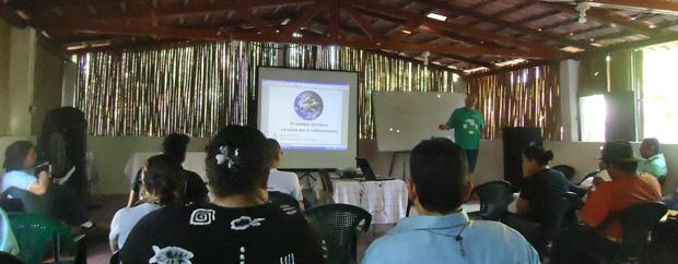 Man giving a talk in a rural hut