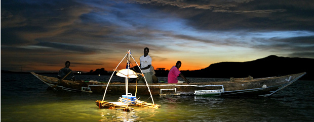 Kenianische Fischer auf einem Boot im Dunkeln, auf einer Schwimminsel davor eine elektrische Lampe.