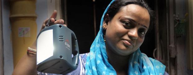 Frau in blauem Shalwa hält eine Lampe in die Kamera