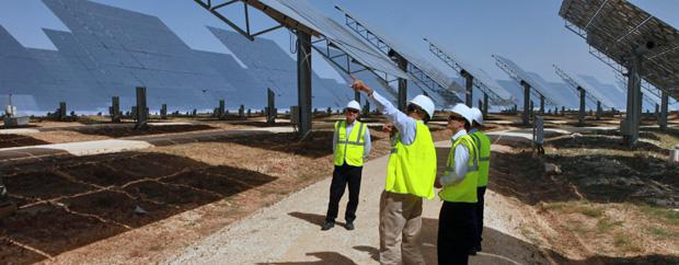 Männer in Warnwesten und Helmen begutachten Solarpaneele