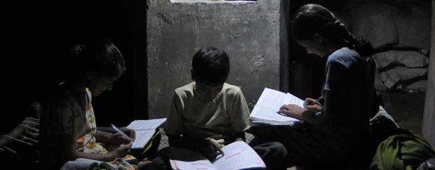Kinder im Halbdunkel über Bücher gebeugt